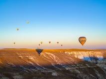 Ballons à air chauds colorés volant au-dessus de la vallée chez Cappadocia Images stock