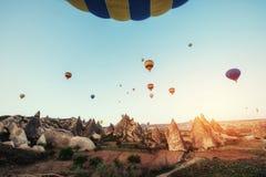 Ballons à air chauds colorés volant au-dessus de la vallée rouge chez Cappadocia, Photographie stock