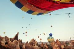 Ballons à air chauds colorés volant au-dessus de la vallée rouge chez Cappadocia, Photos stock