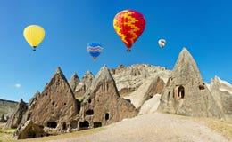 Ballons à air chauds colorés volant au-dessus des falaises volcaniques chez Cappadocia Images stock
