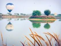Ballons à air chauds colorés volant plus de sur les gisements de fleur colorés photographie stock libre de droits