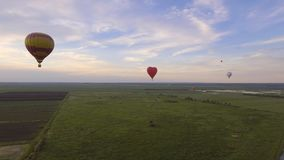 Ballons à air chauds dans le ciel au-dessus d'un champ Image stock