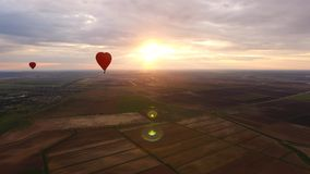Ballons à air chauds dans le ciel au-dessus d'un champ Photo libre de droits