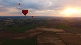 Ballons à air chauds dans le ciel au-dessus d'un champ Image libre de droits