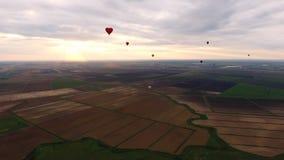 Ballons à air chauds dans le ciel au-dessus d'un champ Images stock