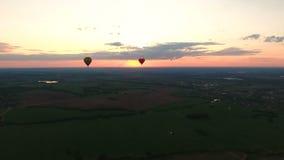 Ballons à air chauds dans le ciel au-dessus d'un champ Silhouette d'homme se recroquevillant d'affaires clips vidéos