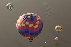 Ballons à air chauds multiples au-dessus de l'eau Photographie stock
