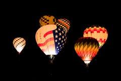Ballons à air chauds rougeoyants colorés volant la nuit sur un fond noir de ciel nocturne images libres de droits