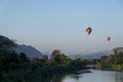 Ballons à air chauds volant au-dessus de la rivière Nam Song au lever de soleil Vang Vieng, Laos Photos stock