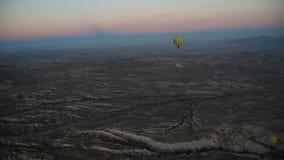 Ballons à air chauds volant au-dessus de la vallée au lever de soleil Cappadocia La Turquie banque de vidéos