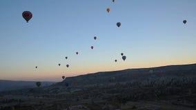 Ballons à air chauds volant au-dessus de la vallée au lever de soleil Cappadocia La Turquie clips vidéos