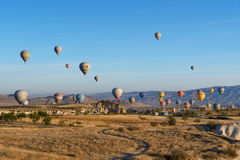 Ballons à air chauds volant au-dessus de la vallée pendant le matin Cappadocia La Turquie Photographie stock libre de droits