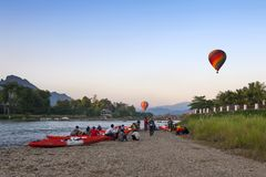 Ballons à air chauds volant au-dessus de Nam Song River et des kayaks de touriste dans Vang Vieng, station touristique populaire  Photo stock