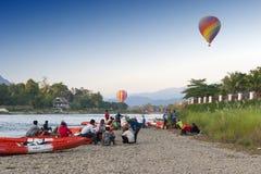Ballons à air chauds volant au-dessus de Nam Song River et des kayaks de touriste dans Vang Vieng, station touristique populaire  Photo libre de droits