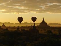 Ballons à air chauds volant par la scène de lever de soleil au-dessus du complexe de temple de Bagan Photographie stock