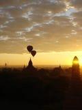 Ballons à air chauds volant par la scène de lever de soleil au-dessus du complexe de temple de Bagan Images libres de droits
