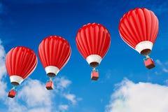 Ballons à air d'un rouge ardent volant au-dessus du ciel nuageux Photo libre de droits