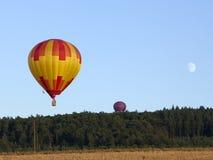 Ballons à air et lune chauds au-dessus de forêt et de zone Image stock