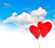 Ballons à air rouges en forme de coeur en ciel bleu Rose rouge Photo stock