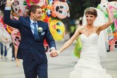 Ballons εκμετάλλευσης ζευγών χαμόγελου στην πόλη υποβάθρου στοκ εικόνα