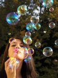 Ballons. Young woman blowing soap balloons royalty free stock photos