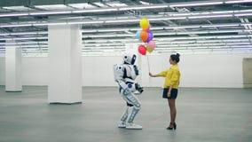 Ballons colorés de cadeaux amicaux de fille à un cyborg blanc clips vidéos