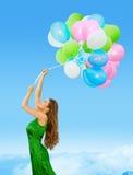 Ballons colorés par femme, ciel de Flying Blue de jeune fille Images stock