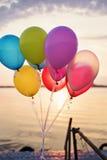 Ballons colorés sur le pont à la mer et à un beau coucher du soleil Ballons de fête d'anniversaire Image libre de droits