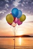 Ballons colorés sur le pont à la mer et à un beau coucher du soleil Ballons de fête d'anniversaire Photos stock