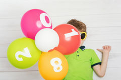 Ballons d'arc-en-ciel dans la main d'enfant Images stock