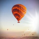 Ballons dans le ciel au-dessus de Cappadocia au lever de soleil Images stock