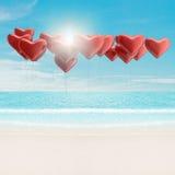 Ballons de coeur au-dessus de la mer Images stock
