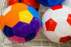 Ballons de football colorés dans le supermarché Images stock