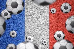 Ballons de football sur un drapeau français texturisé d'herbe Image stock