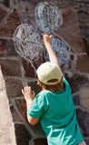 Ballons de retrait de garçon sur un mur en pierre Photo stock