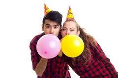Ballons de soufflement de jeunes couples Photos libres de droits