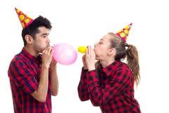 Ballons de soufflement de jeunes couples Images stock