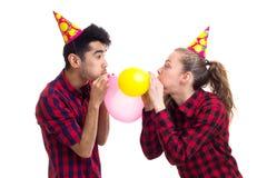 Ballons de soufflement de jeunes couples Photo stock