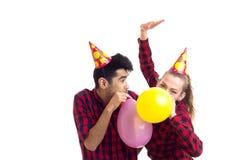 Ballons de soufflement de jeunes couples Image libre de droits