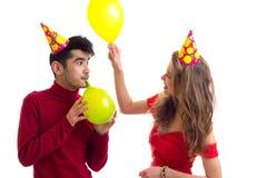 Ballons de soufflement de jeunes couples Photographie stock