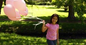 Ballons de transport de petite fille pour la conscience de cancer du sein en parc banque de vidéos
