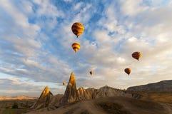 Ballons die in zonsopgang in Cappadocia Turkije toenemen Stock Foto's