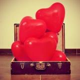Ballons en forme de coeur dans une vieille valise Image libre de droits