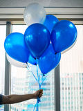Ballons with hand holding in office. Celebration work place concept Stock Photos