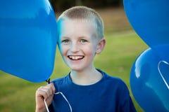 Ballons heureux de fixation de petit garçon Photographie stock libre de droits