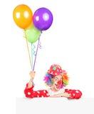 Ballons mâles de wqith de clown posant derrière le panneau image stock