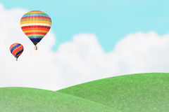 Ballons over grass hill. Royalty Free Stock Image