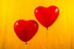 Ballons rouges de coeur sur le fond jaune Image libre de droits