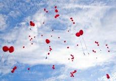 Ballons rouges volant au ciel Image stock