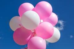 Ballons, roze en wit op een achtergrond van blauwe hemel met wolken stock afbeelding